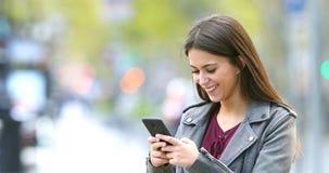 El mandar un SMS adolescente de la moda sonriente en el teléfono en la calle almacen de video