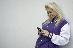El mandar un SMS adolescente en smartphone Foto de archivo
