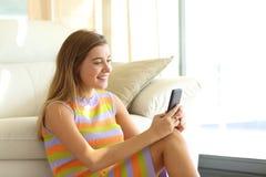 El mandar un SMS adolescente en un teléfono elegante en casa Fotos de archivo