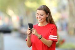 El mandar un SMS adolescente feliz en el teléfono en la calle Imagen de archivo libre de regalías