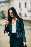 El mandar un SMS casual hermoso joven/que invita de la mujer a su teléfono celular Foto de archivo libre de regalías