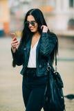 El mandar un SMS casual hermoso joven/que invita de la mujer a su teléfono celular Imágenes de archivo libres de regalías