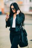 El mandar un SMS casual hermoso joven/que invita de la mujer a su teléfono celular Fotos de archivo