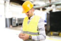 El mandar un SMS de charla de la ojeada del empleado del obrero en smartphone fotos de archivo
