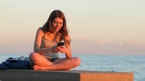 El mandar un SMS de estudiante adolescente en la puesta del sol en la playa