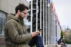 El mandar un SMS de trabajo del hombre joven en un teléfono móvil que se sienta en un banco en el cuadrado Imagen de archivo libre de regalías