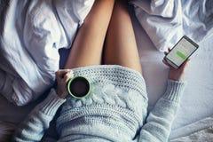 El mandar un SMS en cama fotos de archivo