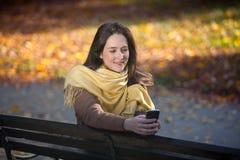 El mandar un SMS en el parque Foto de archivo libre de regalías