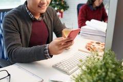 El mandar un SMS en el trabajo Foto de archivo libre de regalías