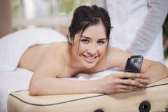 El mandar un SMS en un balneario de la belleza Imagenes de archivo