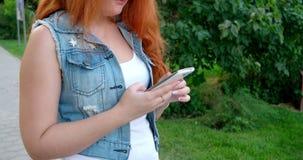 El mandar un SMS en un smartphone Mujeres que trabajan con almacen de metraje de vídeo