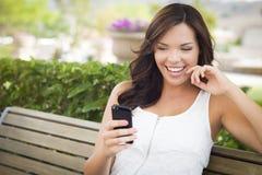 El mandar un SMS femenino adolescente hermoso en el teléfono celular al aire libre Fotografía de archivo