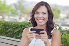 El mandar un SMS femenino adolescente joven sonriente en el teléfono celular al aire libre Imagen de archivo