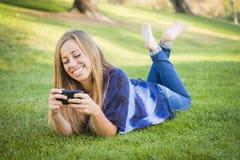 El mandar un SMS femenino adolescente social en el teléfono celular al aire libre Fotografía de archivo