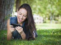 El mandar un SMS femenino joven de la raza mixta en el teléfono celular afuera Foto de archivo