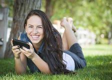 El mandar un SMS femenino joven de la raza mixta en el teléfono celular afuera Imagen de archivo