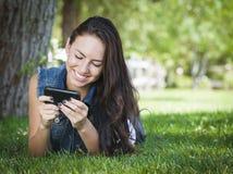 El mandar un SMS femenino joven de la raza mixta en el teléfono celular afuera Fotografía de archivo