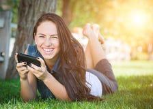 El mandar un SMS femenino joven de la raza mixta en el teléfono celular afuera en el Gra Foto de archivo libre de regalías