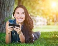 El mandar un SMS femenino joven de la raza mixta en el teléfono celular afuera en el Gra Fotografía de archivo libre de regalías
