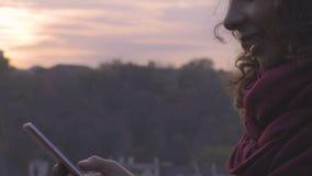 El mandar un SMS femenino multirracial sonriente en el teléfono móvil al aire libre, redes sociales metrajes