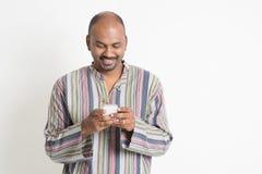 El mandar un SMS indio casual maduro del hombre Fotografía de archivo