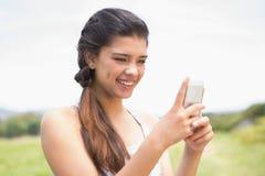El mandar un SMS moreno bonito en el parque Foto de archivo