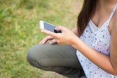 El mandar un SMS moreno bonito en el parque Imagenes de archivo