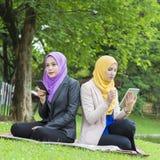 El mandar un SMS ocupado de dos estudiantes universitarios con su smartphone mientras que descansa en el parque Imagen de archivo