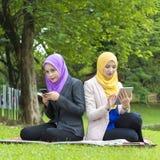 El mandar un SMS ocupado de dos estudiantes universitarios con su smartphone mientras que descansa en el parque Fotografía de archivo