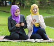 El mandar un SMS ocupado de dos estudiantes universitarios con su smartphone mientras que descansa en el parque Fotos de archivo libres de regalías