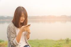 El mandar un SMS que habla de la mujer seria infeliz escéptica triste trastornada del retrato del primer en el teléfono Foto de archivo