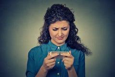 El mandar un SMS que hablaba de la mujer seria triste trastornada en el teléfono descontentó con la conversación Foto de archivo libre de regalías