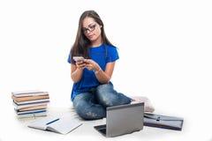 El mandar un SMS que se sienta de la muchacha del estudiante en smartphone Imagen de archivo libre de regalías