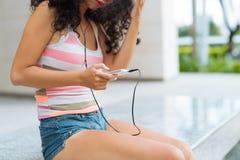 El mandar un SMS y el escuchar la música Imagen de archivo