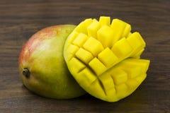 El mango dos cortó vida tropical de las vitaminas naturales amarillas verdes rojas frescas maduras del cubo en la madera imagenes de archivo