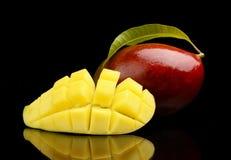 El mango maduro con la rebanada y la hoja aisló el fondo negro Fotos de archivo libres de regalías