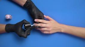 El manicuro en guantes de goma negros pinta los clavos del cliente con el esmalte de u?as protector transparente en el fondo, cla almacen de video