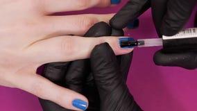 El manicuro pinta los clavos del cliente con el esmalte de uñas transparente en el fondo rosado, maquillaje y los clavos, se cier metrajes