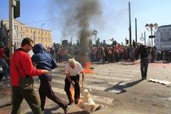 El manifestante intenta apagar el fuego en sus piernas Imagenes de archivo