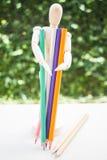 El maniquí de madera y el color dibujan a lápiz en la tabla de trabajo del artista Imagen de archivo libre de regalías