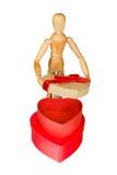 El maniquí de madera abre la caja de regalo en forma de corazón Imagen de archivo libre de regalías