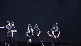 El manojo de adolescentes lindos y las muchachas en ropa y casquillos negros bailan en etapa almacen de metraje de vídeo