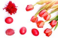 El manojo de flores cerca arquea y pica los huevos de Pascua adornados Imagenes de archivo
