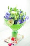 El manojo de flores en un florero fijó con dos corazones de cristal rojos Fotografía de archivo libre de regalías