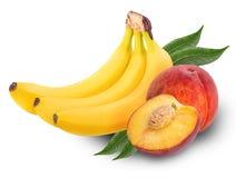 El manojo de los plátanos y del melocotón dulce uno cortó por la mitad con las hojas Imagen de archivo libre de regalías