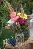 El manojo de otoño colorido florece en el tarro de cristal con la uva Foto de archivo