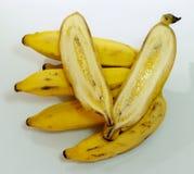 El manojo de plátanos amarillos maduros así como uno cutted en el centro Foto de archivo