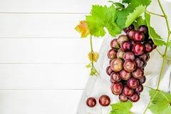 El manojo de uvas con las hojas frescas del verde y el lino de tabla en el plano de madera blanco del fondo ponen la visión super Fotografía de archivo libre de regalías