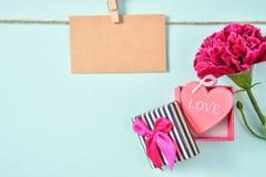 El manojo del clavel del día del ` s de la madre de mayo de ramo de las flores con el regalo del amor y la tarjeta de felicitació Fotografía de archivo libre de regalías