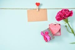 El manojo del clavel del día del ` s de la madre de mayo de ramo de las flores con el regalo del amor y la tarjeta de felicitació Imagen de archivo libre de regalías